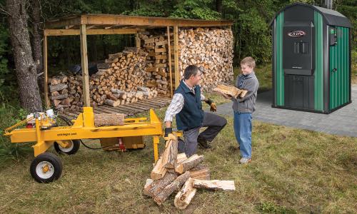Un niño y su padre cortando leña para la caldera.