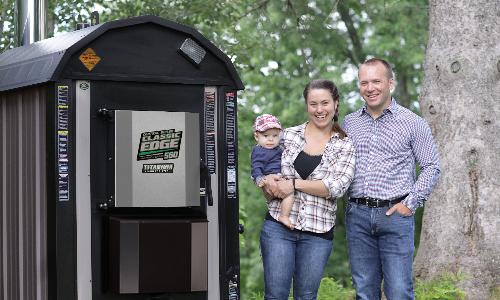 Una familia feliz junto a su caldera de instalación exterior.