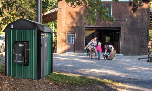 Una caldera de leña de instalación exterior instalada a varios metros del hogar al que está conectada.